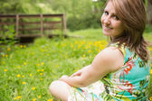 Cute young woman relaxing in field — Stock Photo