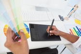 Designer working at desk using digitizer and colour sample — Stock Photo