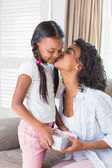 Pretty mother offering daughter a gift — Stock Photo