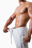 Mid section of a muscular man in an over sized pants — Stock Photo