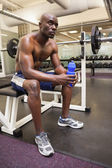 Muscular man with energy drink in gym — Foto de Stock