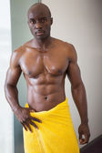 Muscular man wrapped in yellow towel — Stock Photo