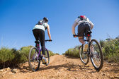 Active couple cycling uphill on a bike ride in the country — Stock Photo