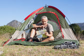 Happy camper looking at map sitting in his tent — Stock Photo