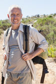 Handsome hiker smiling at camera in the countryside — Stock Photo