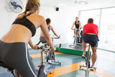Spin class working out with motivational instructor — Stok fotoğraf
