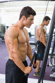 Shirtless muscular man using triceps pull down in gym — Stock Photo
