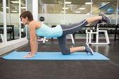 Fit brunette doing pilates on exercise mat — Stok fotoğraf