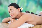 Brunette enjoying hot stone massage — Stok fotoğraf