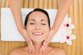Brunetta sorridente, godersi un massaggio facciale — Foto Stock