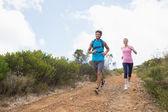 Coppia fare jogging lungo un sentiero di montagna — Foto Stock