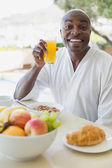 Handsome man in bathrobe having breakfast outside — Stock Photo