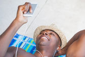 Shirtless man smiling and listening to music on smartphone — Stock Photo
