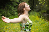 Woman with arms outstretched in field — Foto de Stock
