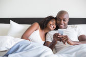 Happy couple cuddling in bed with smartphone — Stock Photo