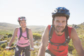 Fit cyclist couple riding together on mountain trail — Stock Photo