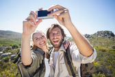 Couple on mountain terrain taking selfie — Stock Photo