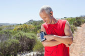 Fit man changing the song on his music player on mountain trail — Stockfoto