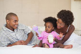 Happy parents and baby girl sitting on bed together — Stock Photo