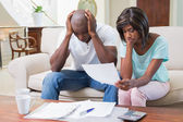 Stressed couple calculating bills on the couch — Stockfoto