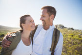 Hiking couple embracing and smiling on country terrain — Stok fotoğraf
