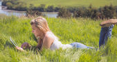 Pretty blonde lying on grass using her tablet — Stock Photo