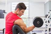 Gespierde man uitoefenend met halter in gym — Stockfoto