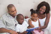 Happy family lying on bed using tablet pc — Stock Photo