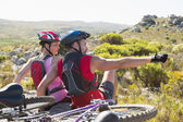 Fit cyclist couple sitting at the summit looking around — Stock Photo