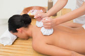Beautiful brunette enjoying a herbal compress massage — Stock Photo