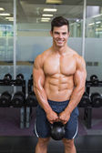 Muscular man lifting kettle bell in gym — Stock Photo