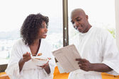 Happy couple having breakfast together in bathrobes — Stock Photo