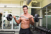 Smiling shirtless muscular man lifting barbell in gym — Stock Photo