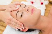 Smiling brunette enjoying a head massage — Стоковое фото