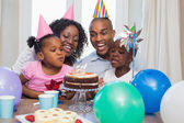 Happy family celebrating a birthday together at table — Stockfoto