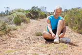 Smiling jogger tying his shoelace on mountain trail — Stock Photo