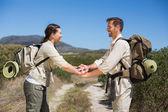 Caminhadas casal colocando as mãos juntas na trilha país — Foto Stock