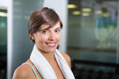Fit brunette smiling at camera with towel around shoulders — Stock Photo