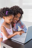 Cute daughter using laptop at desk with mother — Stock Photo