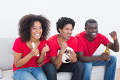Football fans in red sitting on couch cheering — Stock fotografie