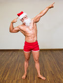 Full length of a body builder in santa costume — Stok fotoğraf