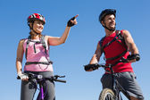 Fit cyclist couple standing at the summit — Stock Photo