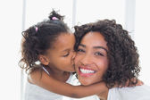 Pretty mother with her daughter kissing her cheek — Stock Photo
