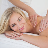 Pretty blonde enjoying a massage smiling at camera — Stock Photo