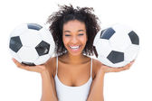 Pretty girl holding footballs and laughing at camera — Stock Photo