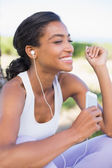Fit woman sitting down listening to music — Stock Photo