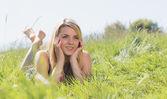 Hezká blondýnka v letní šaty, ležící na trávě — Stock fotografie
