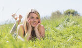 Pretty blonde in sundress lying on grass  — Foto de Stock