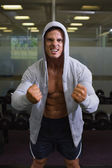 Muscular man clenching fists in health club — Stock Photo