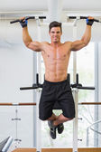 Shirtless male body builder doing pull ups — Stock Photo